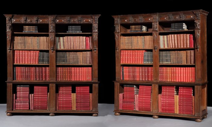 A massive, pair of mid-19th century, 'antiquarian', oak, bookcases in the English, Renaissance, Revival style, inspired by the chimneypiece from the Old Palace, Bromley-by-Bow, dated 1606 by Vredeman de Vries, now in the British Galleries at the V&A, Museum, and the wooden Screen in the Great Hall at Knole Park, Kent